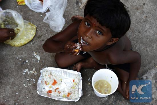 File Photo: A child of a street bagger family eats gifted food on the World Food Day in the eastern Indian state Orissa's capital city Bhubaneswar, Oct. 16, 2014. (Xinhua/Stringer)