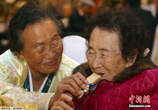 Kim Ri Nam, 83, (left), who lives in DPRK, gives a cookie to her South Korean older sister, Kim Yu-nam, 89, during the reunion of separated families held at DPRK's Diamond Mountain resort on October 24, 2015. (Photo/Agencies)