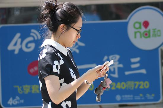 A mobile phone user walks past a logo of China Mobile's 4G service in Qingdao, Shandong province. (Photo/China Daily)