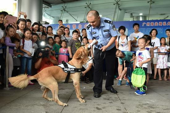 A detection dog signals to its handler at an anti-drug demonstration in Guangzhou on Sunday. Tuesday marks International Day Against Drug Abuse and Illicit Trafficking. (Photo/Xinhua)