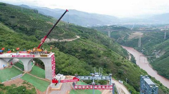An aerial photo taken on June 22, 2018, shows construction workers lift a steel girder by crane as they build a bridge across the Yuanjiang River along the China-Laos Railway in Yuxi, southwest China's Yunnan Province. /Xinhua Photo