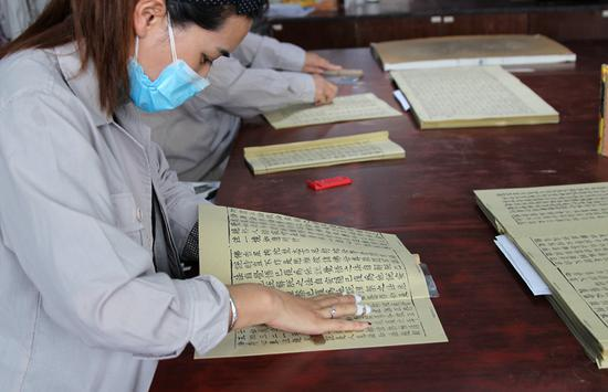 Employees prepare printed copies of the Buddhist classics at Yangzhou Classics Reproductions Co on Wednesday. (Photo/CHINA DAILY)
