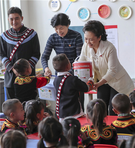 Peng Liyuan, the wife of President Xi Jinping, brings gifts to children from the Yi ethnic group in the Liangshan Yi autonomous prefecture, Sichuan province, on Thursday. She encouraged them to develop healthy habits in childhood to avoid illnesses and disease later. [Photo provided to China Daily]