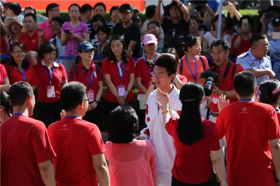 A candidate for this year's national college entrance exam, the gaokao, is cheered up by teachers and parents before entering an exam site in Beijing on June 7, 2018. (Photo by Wang Jing/chinadaily.com.cn)