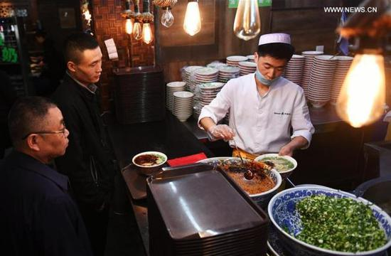A chef prepares a bowl of beef noodle at a noodle restaurant in Lanzhou, capital of northwest China's Gansu Province, April 12, 2017. As a piece of name card of Lanzhou City, beef noodle is an indispensable food of local people. There are more than 1,000 beef noodle cookshops in Lanzhou and they can sell over one million bowls of beef noodle every day. (Photo/Xinhua)