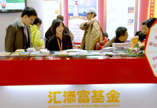 A fund manager from an asset management company oversees brochures about various financial products, to be given away to prospective individual investors, at the company's stall at the 7th Money Fair held in Shanghai earlier this year. (Photo provided to China Daily)