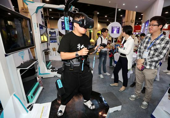 A visitor checks out a virtual reality headset at an exhibition for unicorns in Hangzhou, capital of Zhejiang Province. (Photo by Lin Yunlong/For China Daily)