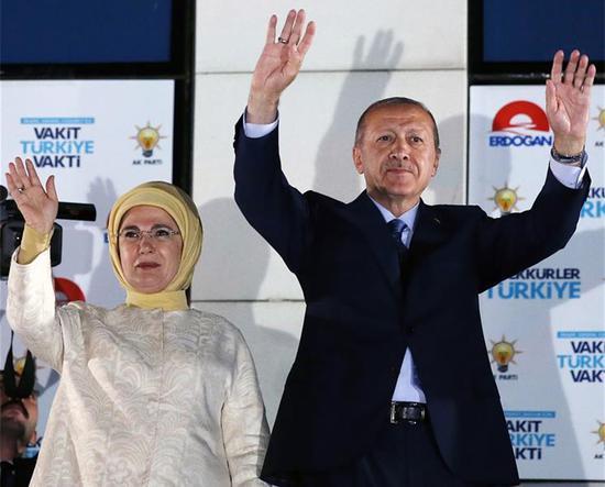 2018年6月25日,土耳其总统雷杰普·塔伊普·埃尔多安(Recep Tayyip Erdogan)在土耳其安卡拉的正义与发展党(AKP)总部前举行的集会上,与妻子一起向支持者致意。(新华社/穆斯塔法·卡亚)