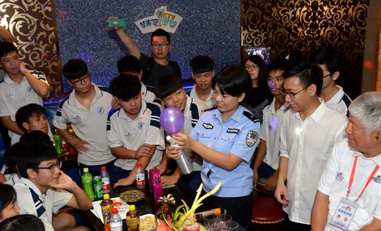 A police officer teaches teenagers a lesson on keeping away from drugs at a karaoke bar in Guangzhou, Guangdong Province, on Tuesday. She advised the teens to raise their awareness of drugs-even anesthetics such as nitrous oxide, or laughing gas-which is being abused as a drug and may be found in balloons at entertainment venues. (QIAN WENPAN/FOR CHINA DAILY)