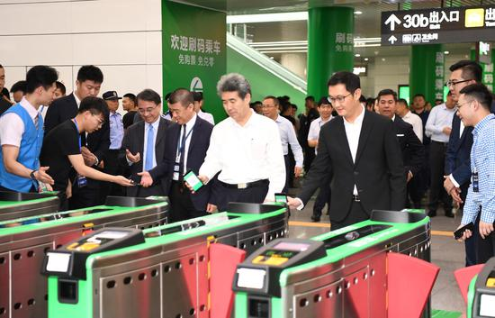 ony Ma (right), founder and CEO of Tencent, Liu Qingsheng (second from right), executive vice-mayor of Shenzhen, and other officials and business leaders use WeChat QR code scanning at a subway entrance in Shenzhen on May 8. (Photo/China News Service)