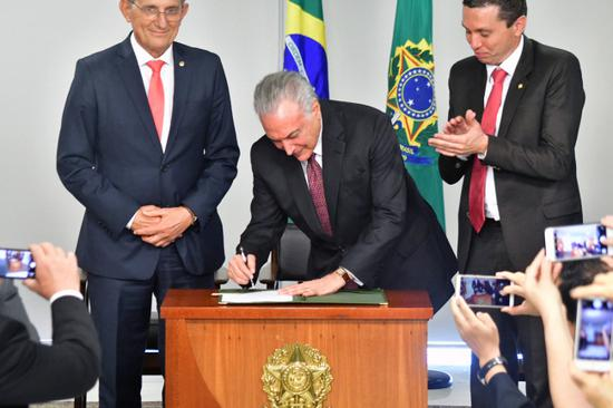 The photo, taken on June 26, 2018, shows Brazilian President Michel Temer signing a bill to recognize August 15th as National Chinese Immigration Day. [Provided to China Plus]