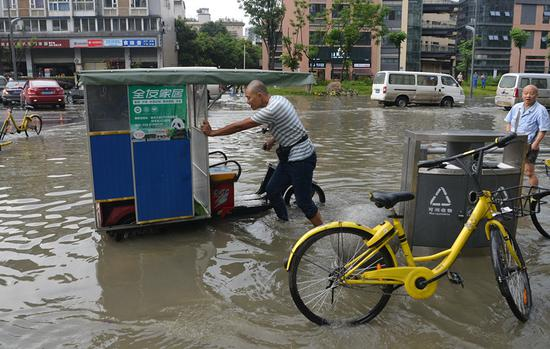 A man pushes his vehicle in a flooded street in Chengdu, Sichuan Province, on Thursday. (PHOTO/CHINA NEWS SERVICE)
