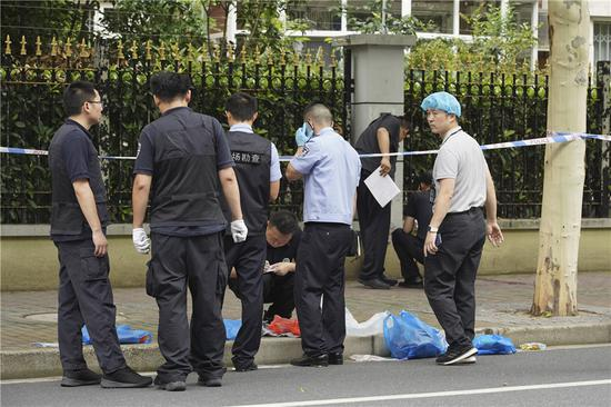 Police examine the site of a knife attack that occurred on Thursday morning in downtown Shanghai leaving two boys dead and another boy and a parent wounded. (Gao Erqiang/China Daily)