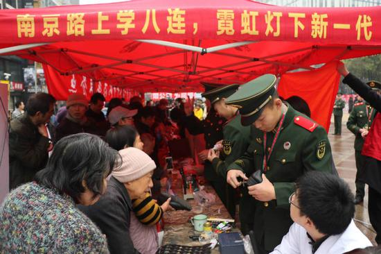 Soldiers of the squad provide voluntary services to Shanghai residents on the city's Nanjing Road. (ZHANG HAI/FOR CHINA DAILY)