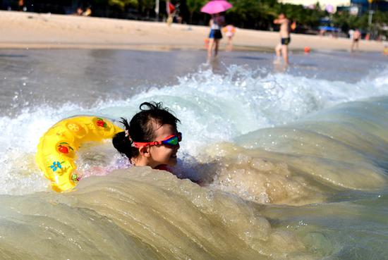 A child enjoys a cool moment in the ocean waves at a scenic zone in Sanya, Hainan Province, on Sunday. Several cities in the province have issued heat alerts recently. (Photo/ China Daily)