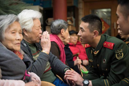 Members of the squad talk with residents of a nursing home in Shanghai during a regular visit. (ZHANG HAI/FOR CHINA DAILY)