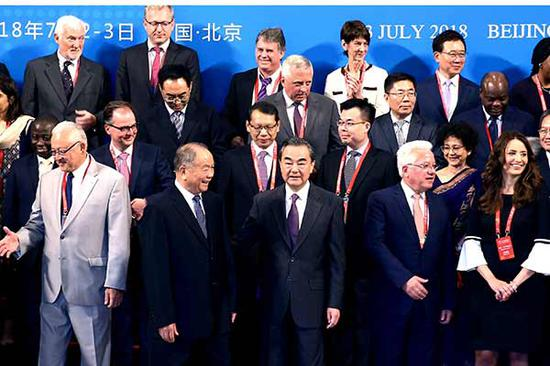 State Councilor and Foreign Minister Wang Yi (center) takes a group photo with foreign guests before the opening of the Forum on Belt and Road Legal Cooperation in Beijing on Monday. Wang said a dispute settlement mechanism for Belt and Road will be established at an early date. (Photo by Zou Hong/China Daily)