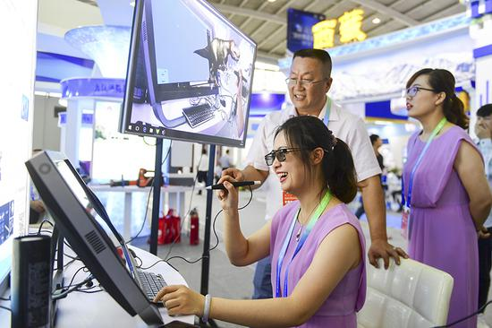 Exhibitors demonstrate virtual reality education materials during a tech exhibition in Shenyang, Liaoning province, on Wednesday. (An Chenhao/For China Daily)