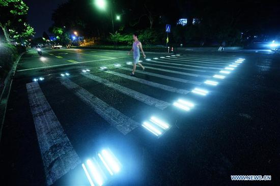 Lamps light up along pedestrian crossing at night in Hangzhou