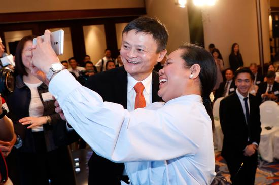 Jack Ma, founder and chairman of Alibaba Group Holding Ltd, poses for a photo with the first user of blockchain-enabled AlipayHK in Hong Kong on June 25, after she sent money through AlipayHK to Gcash, a Philippine e-payment application, at the launch event of the cross-border e-payment service. (Photo/XU KANGPING FOR CHINA DAILY)