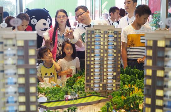 A property model attracts visitors during an industry expo in Dongguan, Guangdong province. [Photo by An Dong / For China Daily]