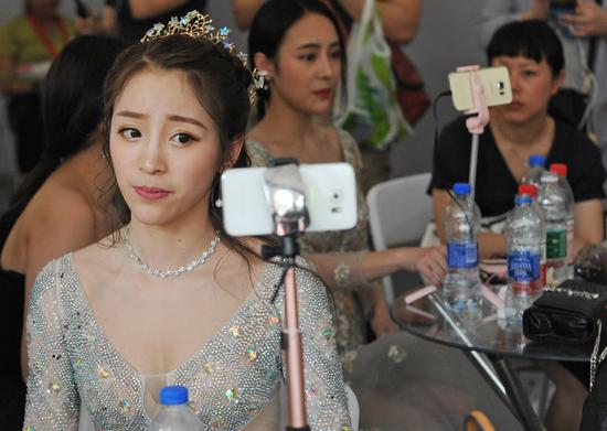 An online celebrity reacts for her followers via a livestreaming app in Wuhan, capital of Hubei province. [Photo by Miao Jian/For China Daily]