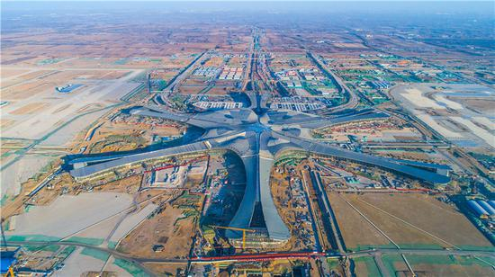 An aerial photo shows the construction site of Beijing's new airport in southern Daxing district in Beijing. The new international airport is taking shape and already has a roof in March. (Photo by Yang Zhiyong/chinadaily.com.cn)