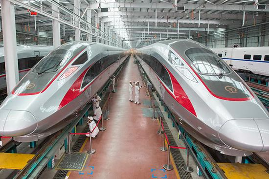 Workers check Fuxing bullet trains in the assembly workshop of CRRC Qingdao Sifang Co in Qingdao, Shandong Province, in June.(Photo by Wu Huapeng/Xinhua)
