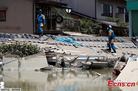 Police officers check submerged and destroyed houses in a flooded area in Mabi town in Kurashiki, Okayama Prefecture, Japan, July 10, 2018. (Photo/Agencies)