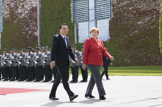 Premier Li Keqiang is escorted by German Chancellor Angela Merkel on Monday at a welcoming ceremony in Berlin. (Photo/Xinhua)