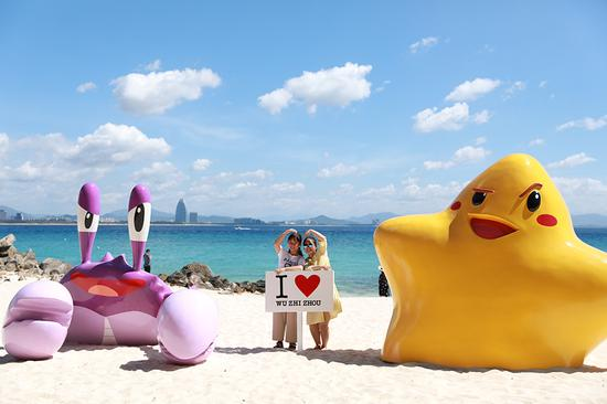 Two women pose for a photo at the beach of Wuzhizhou island in Sanya, Hainan Province. (Photo provided to China Daily)