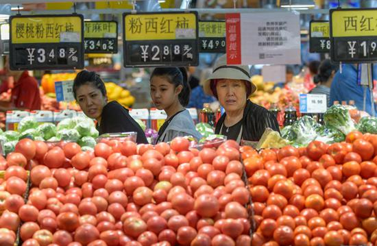 Shoppers choose vegetables at a supermarket in Taiyuan, capital of Shanxi province. (Photo by Wu Junjie/China News Service)