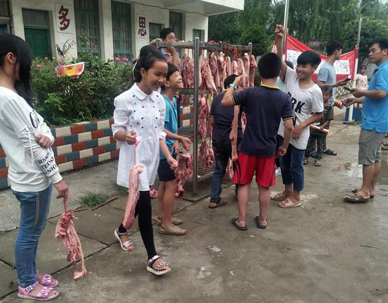 Students take home pork as an award at Zhiliao Primary School in Sanjiang county in the Guangxi Zhuang autonomous region on Friday. Those who scored over 80 in their Chinese and math final exams were awarded 1 kilogram of pork. The prize has been popular. (Photo/China News Service)
