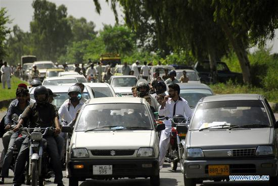Vehicles and local residents are seen on road on World Population Day in Islamabad, capital of Pakistan on July 11, 2018. The World Population Day is observed on July 11 every year to raise awareness of global population issues.(Xinhua/Saadia Seher)