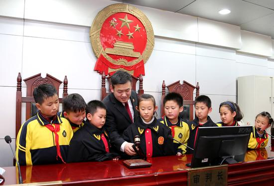 Gao Guangshi, a judge at Shizhong district court, Zaozhuang city, Shandong province, shows primary school students how he uses his gavel. Students are regularly invited to visit the court to learn about proceedings and take part in mock trials. (Photo: For China Daily/Ji Zhe)