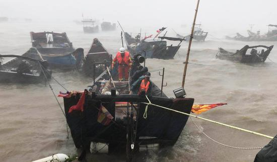 Firefighters use a boat to evacuate a stranded fisherman off Lianjiang county of Fujian Province's capital, Fuzhou, on Wednesday. (For China Daily)