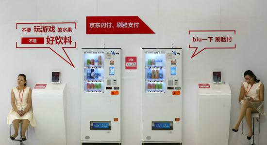 Two beverage vending machines, that use the JD Pay facial recognition technology for payments, are displayed at a JD stand during a recent internet and information security expo in Beijing. (Photo provided to China Daily)