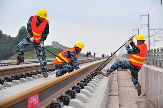 Workers from China Railway Construction Group lay tracks along the Chengdu-Guiyang high-speed railway line. (Photo by Cao Ning/For China Daily)