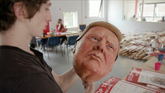 A protester puts the final touches on his Trump mask ahead of Friday's demonstration. /CGTN Photo