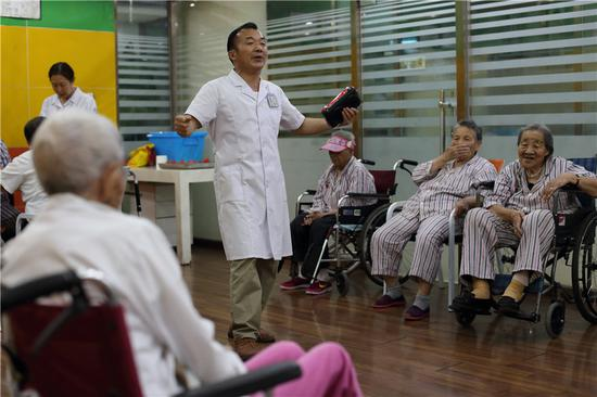 Ouyang Zifan, a carer at Songtang, sings for senior patients. (Photo: China Daily/Wang Jing)