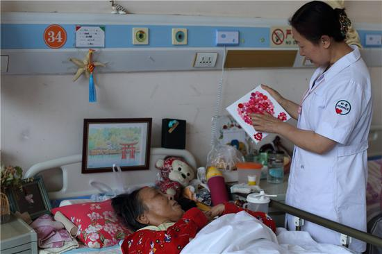 A member of staff at the Beijing Songtang Care Hospital, one of China's first end-of-life centers, chats with a patient.  (Photo: China Daily/Wang Jing)