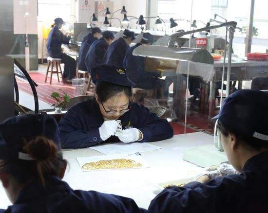 Workers check the quality of gold products at a workshop of Zhaojin Group Co Ltd in Zhaoyuan, Shandong province. (Photo by Ren Haixia / China News Service)
