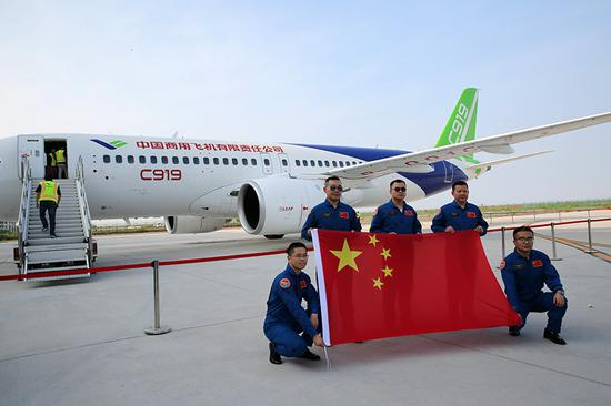 Crew members pose for a photo after a C919 plane's successful completion of a test flight from Shanghai to Dongying, Shandong Province, on July 12. (Photo by Zhou Guangxue/China News Service)