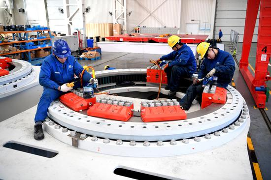 Employees from a subsidiary of China Shipbuilding Industry Corp install clean-energy equipment in Nantong, Jiangsu Province. (Photo/Xinhua)