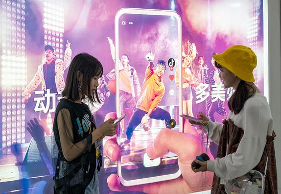 Two women stand near a poster for short-video app Douyin in Shanghai. (Photo/China Daily)