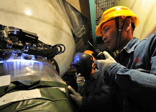 A technician oversees an automatic welding operation at the Ningde nuclear power station in Fujian Province. (Photo/Xinhua)