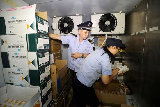 Law enforcement officers check a vaccine storage facility in Rongan county, Guangxi Zhuang autonomous region, on Monday. Market regulators are investigating the vaccine to ensure drug safety. (Photo by Tan Kaixing/For China Daily)