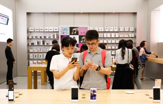 Consumers try out iPhones at an Apple store in Nanjing, Jiangsu Province. In the quarter ended in March, Apple posted revenue of about $13 billion in China, for 21 percent growth year-on-year. (Photo provided to China Daily)
