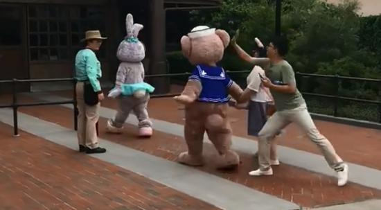 The clips show a man leaping and striking the mascot's head from behind.  (Screenshot of Weibo video)