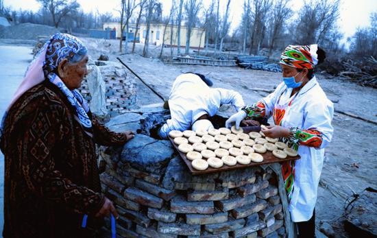 A baker from Yuli county, Xinjiang Uygur autonomous region, sticks naan inside an oven. (Photo Provided To China Daily)